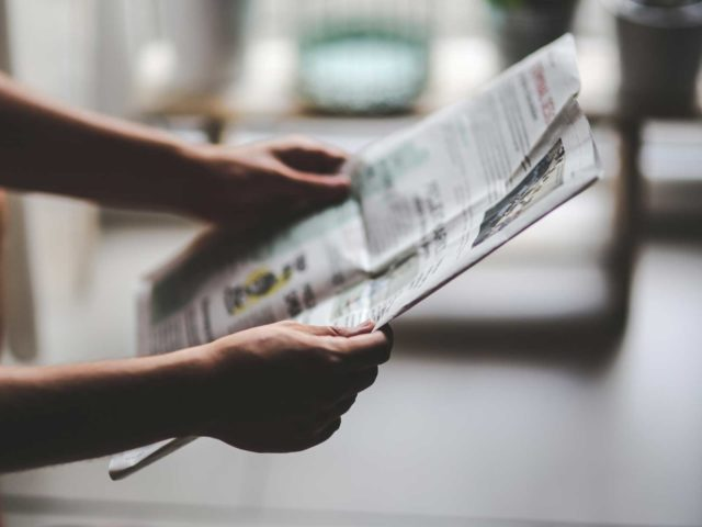 両手で新聞を広げて読む男性